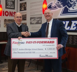 Jordan-Elbridge superintendent Jim Froio was presented with a check for $5,000 during the opening of the Fastrac in Elbridge.
